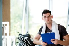 Trainer with clipboard standing in a bright gym. Portrait of a smiling male trainer with clipboard standing in a bright gym Royalty Free Stock Photography