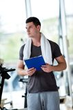 Trainer with clipboard standing in a bright gym. Portrait of a smiling male trainer with clipboard standing in a bright gym Stock Photography