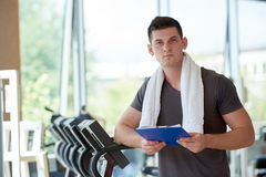 Trainer with clipboard standing in a bright gym. Portrait of a smiling male trainer with clipboard standing in a bright gym Stock Image