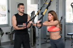 Trainer With Clipboard Woman On Trx Fitness Straps Royalty Free Stock Photography