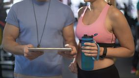 Trainer communicating with female client, creating her personal workout plan. Stock footage stock footage
