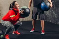 Trainer is controlling the overweight woman who is doing squats stock photo