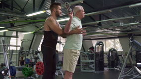 Trainer controls exercises of senior client. Side view of young male trainer controlling exercises of senior client at the gym. Caucasian bearded guy holding his stock video