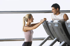 Trainer Conversing With Man On Treadmill. Female trainer conversing with men on treadmill at gym Royalty Free Stock Images