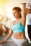 Trainer correcting woman lifting dumbbells stock photo