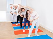 Trainer and customers doing stretching exercise Royalty Free Stock Photos