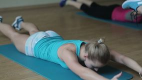 Trainer demonstrating how to do the exercise. Group of girls in fitness center. Group aerobics with trainer. Fitness group exercising in the fitness centre stock footage