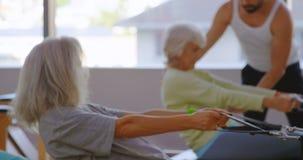 Trainer, der ältere Frauen beim Ausdehnen der Übung 4k unterstützt stock video