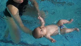 Trainer, der Baby lernt, um zu schwimmen stock video