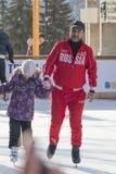 Trainer an der Eisbahn unterrichtet Kinder eiszulaufen Lizenzfreie Stockfotografie