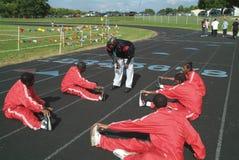 Trainer, der mit dem Bahnteam während thwy Aufwärmen mit exercisesq spricht stockfotografie