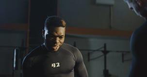 Trainer, der schwarzen Mann während der anhebenden Gewichte stützt stock footage