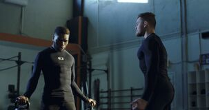 Trainer, der schwarzen Mann während der anhebenden Gewichte stützt stock video