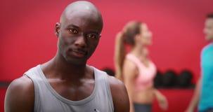 Trainer die bij de camera in crossfitgymnastiek glimlachen stock video