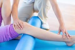 Trainer die met vrouw aan oefeningsmat werken Stock Foto