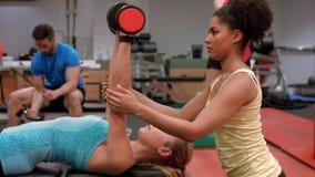 Trainer die vrouw het opheffen gewicht bevlekken stock videobeelden