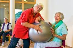 Trainer die vrouw met stabiliteitsbal helpen Stock Afbeeldingen