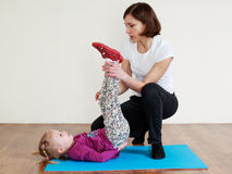 Trainer is doing back exercise with a little girl stock images