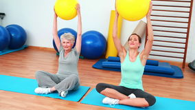 Trainer and elderly client raising exercise balls. At the rehabilitation center stock video footage