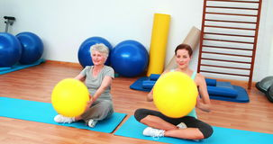 Trainer and elderly client raising exercise balls. At the rehabilitation center stock video
