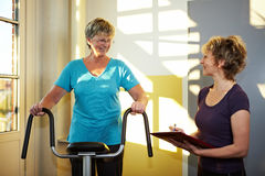 Trainer with eldery woman on. Treadmill in gym Stock Photos
