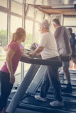Trainer exercise helps elderly couple. Senior couple on. Personal trainer exercise helps elderly couple. Senior couple on the jogging machine. Seniors workout in stock photos