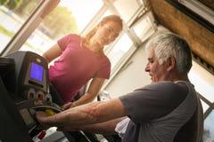 Trainer exercise helps elderly man. Senior man on the j. Personal trainer exercise helps elderly man. Senior men on the jogging machine. Workout in gym royalty free stock images