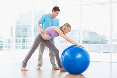 Trainer exercising with blonde pregnant client and exercise ball Stock Photos