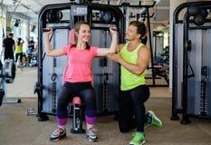 Trainer explaining how to use training machine Royalty Free Stock Photo