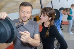 Trainer explaining how to use training machine in gym. Trainer explaining how to use training machine in a gym Royalty Free Stock Image