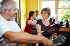 Trainer explaining spinning bike Royalty Free Stock Images