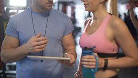 Trainer explaining to client how to build muscle mass and develop strength. Stock footage stock video