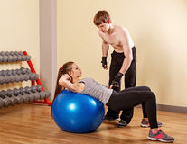 Trainer explains girl exercise on fitball. Personal trainer helping a girl learn to press fitbar. Fitness club. Weight loss program. Health and Fitness Royalty Free Stock Image