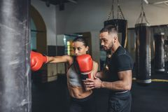 Trainer and female boxer. Handsome young trainer looking at female boxer training with punching bag Stock Photography