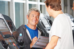 Trainer in fitness center advising senior man Royalty Free Stock Image
