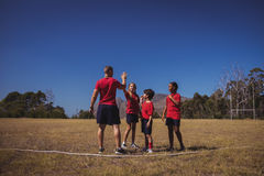 Trainer and girl giving high five to each other during obstacle course training Royalty Free Stock Image