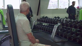 Trainer gives dumbbells to the senior client stock footage