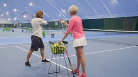 Trainer gives tennis balls to man. Handsome adult caucasian man learns to play tennis. Woman-trainer gives the man a balls and he hit them one by one. Man with stock footage