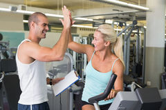 Trainer giving high five to his client on exercise bike at gym Stock Photo