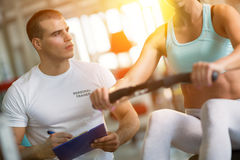 Trainer giving instructions to a woman in a gym Royalty Free Stock Photo