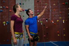 Trainer guiding athlete in climbing wall at gym Royalty Free Stock Photo