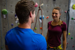Trainer guiding athlete in wall climbing at gym Stock Photos