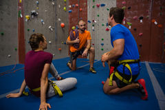 Trainer guiding athletes in wall climbing at gym Royalty Free Stock Photography