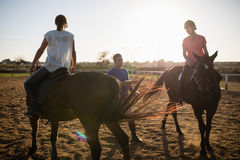 Trainer guiding female friends in riding horse stock images