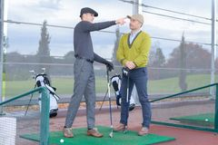 Trainer guiding novice golfer. Trainer guiding a novice golfer royalty free stock photography