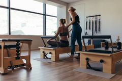 Trainer guiding a pilates woman for correct posture at the gym Royalty Free Stock Images