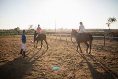 Trainer guiding young women in riding horse royalty free stock photo