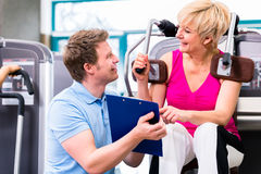 Trainer in gym assisting senior woman exercising Stock Images