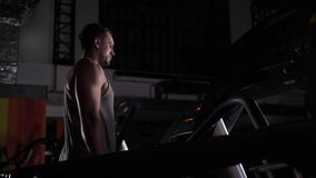 The trainer in the gym stands on the treadmill.