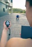 Trainer hand using chronometer to timing man Stock Photo